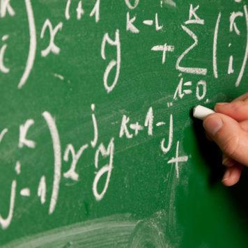 Person writing mathmatical formula on chalkboard