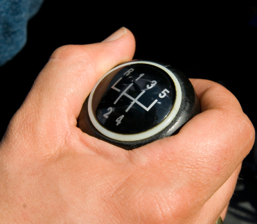 Man's hand shifting gears in car