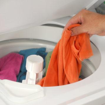 Hand putting laundry into washing maching