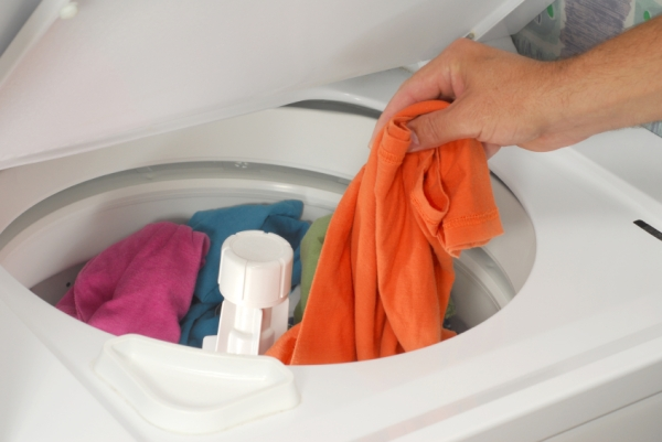 Hand putting laundry into washing maching