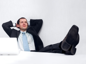 Relaxed business man with feet up on desk