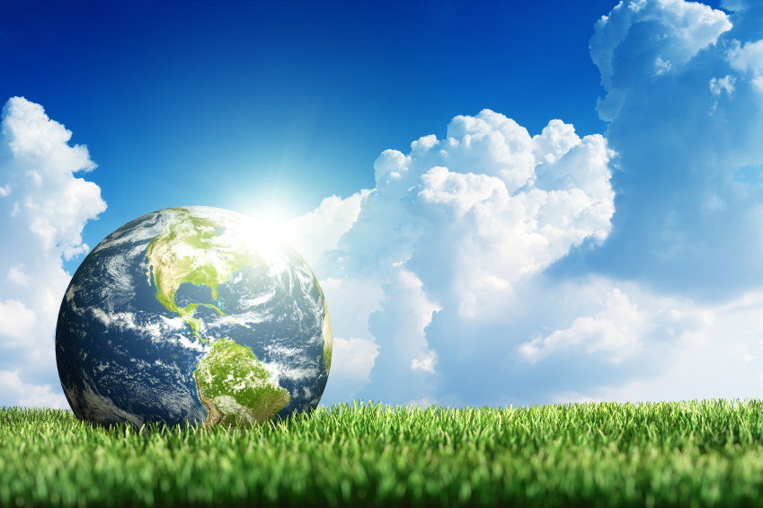 Earth resting on grass with clouds and blue sky in the background