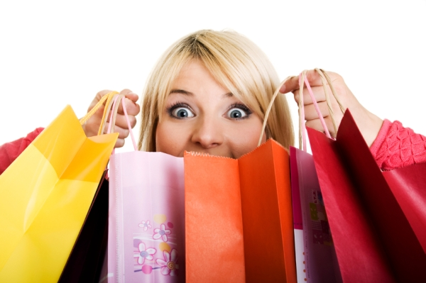 Woman holding shopping bags in front of face