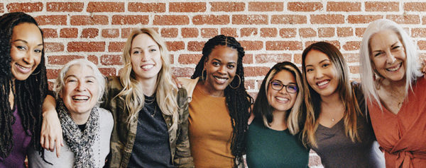 A group of women smiling in front of a brick wall