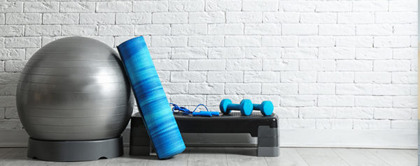 A neat pile of exercise equipment in front of a white brick wall