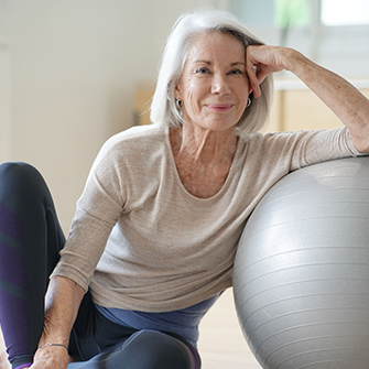 An older woman leaning against an exercise ball