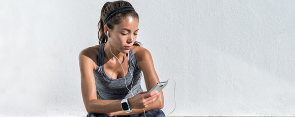 A woman sitting after a run, looking at her phone