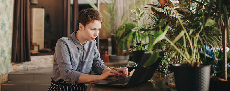 A person sitting at a table using a laptop, surrounded by plants
