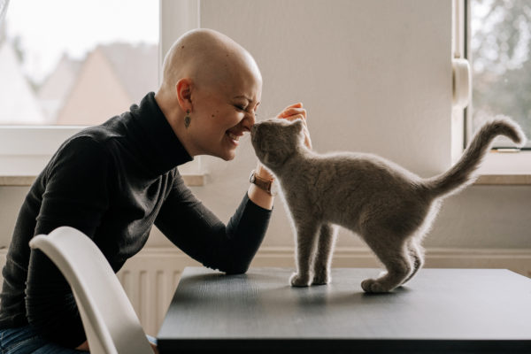A bald woman sits at a table petting and smiling at a grey kitten who has her nose pressed against the woman's.