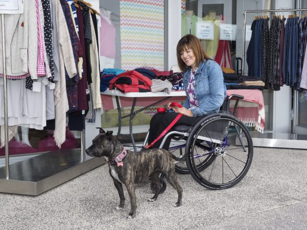 Woman using a wheelchair with her dog on an outing at a coastal marina