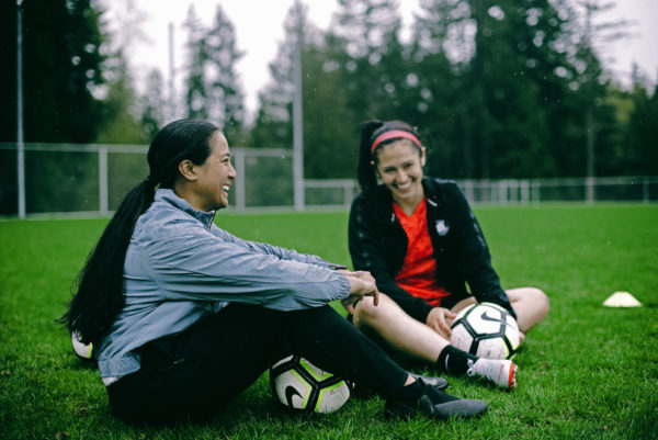 Two women sitting in a soccer field share a laugh. They each have soccer balls by their legs and are wearing jackets.