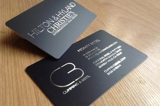 real estate business card with silver text on a black card