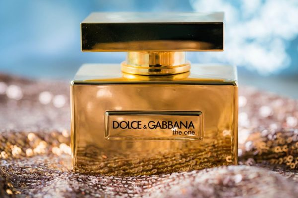 """product beauty shot of a shiny bottle of Dolce & Gabbana """"the one"""" set on a bed of sequined fabric"""