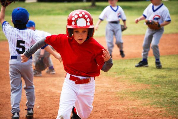 little league baseball player rounding 3rd base.