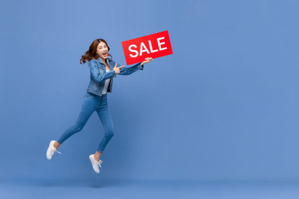 Woman holding a sale promotion sign and jumping in the air with joy