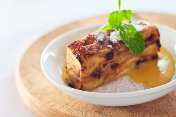 every restaurant website design should include professional photographs of the restaurants own food, like this image of bread-and-butter pudding topped with powdered sugar and a sprig of mint