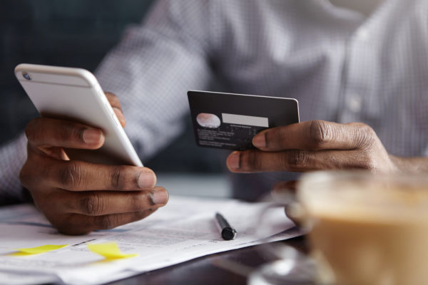 man starting a monthly giving plan by entering credit card information on a cell phone