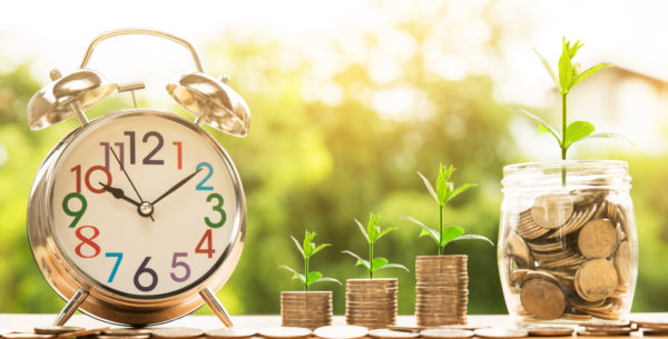 ticking clock next to monthly giving donations (stacks of coins) building and growing