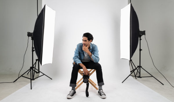 photographer sitting between two large lighting diffusers