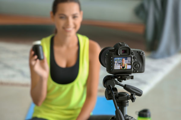 How To Market Health Supplements - Use social media to show off your health supplement like this woman in gym clothes recording a video and holding a bottle of supplements up so the camera can see it