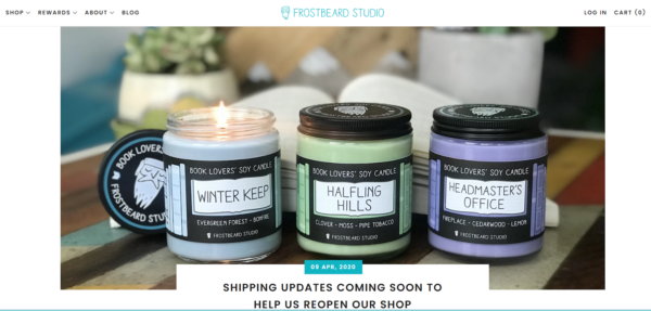 Product Photography Setup - three jar candles of different colors placed together with the candle on the left lit and a background of an open book and potted plants