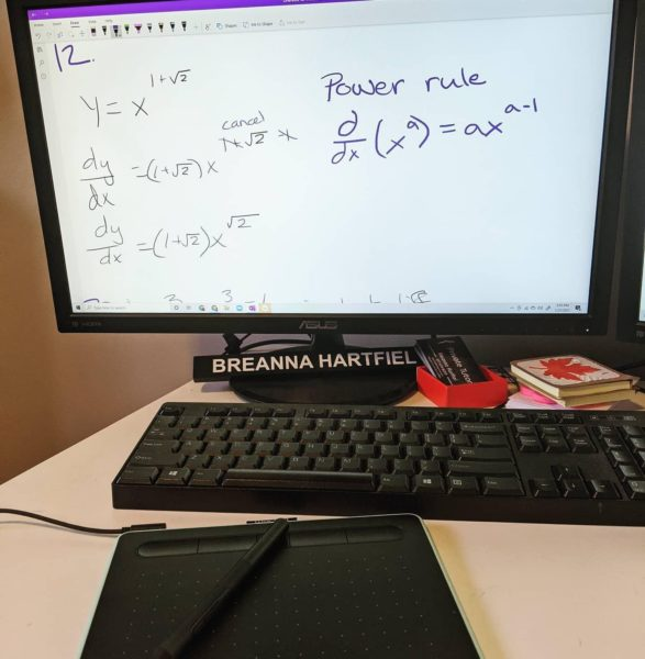 image of Breanna Hartfiel's computer set up, complete with desk nameplate and stack of business cards